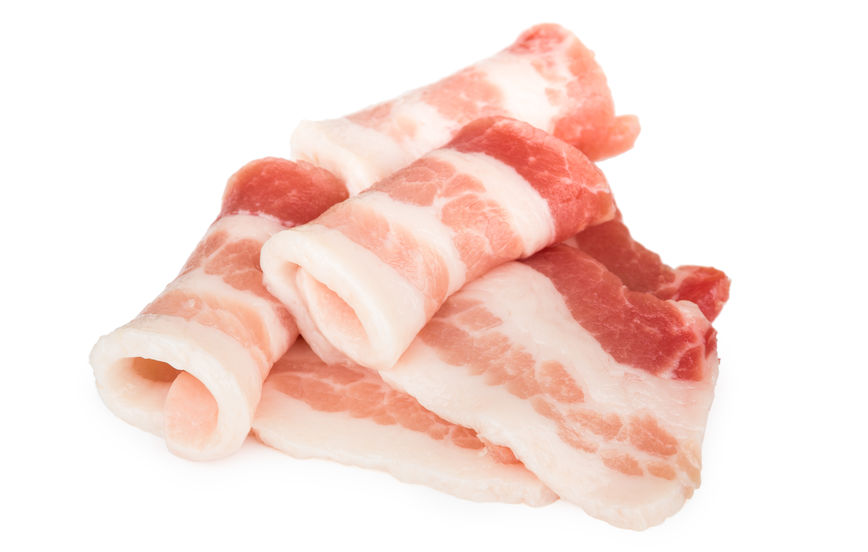 Heap of rolled pieces raw bacon isolated on white background